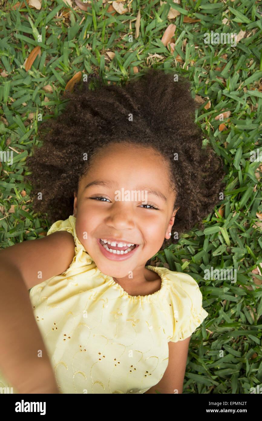 Una chica acostada en la hierba, sonriente y mirando hacia arriba. Imagen De Stock