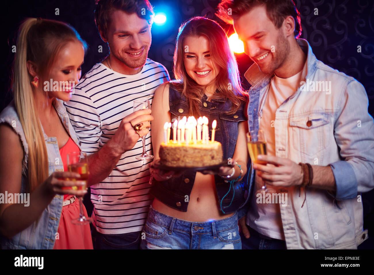 Dos parejas jóvenes con champaña y tarta mirando las velas en la fiesta de cumpleaños Foto de stock