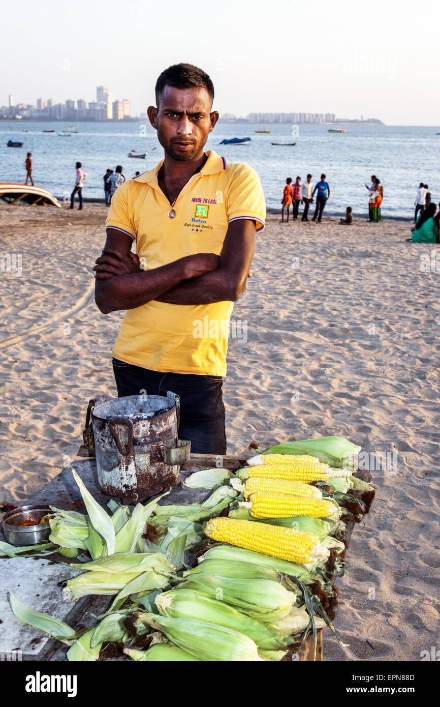 Asia India Mumbai Girgaon Marine Drive Chowpatty Beach proveedor público de mazorca de maíz tostado hombre Imagen De Stock
