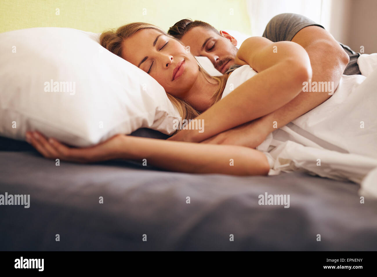 Imagen de una joven pareja durmiendo cómodamente en la cama. Hombre y mujer joven acostado dormido. Imagen De Stock