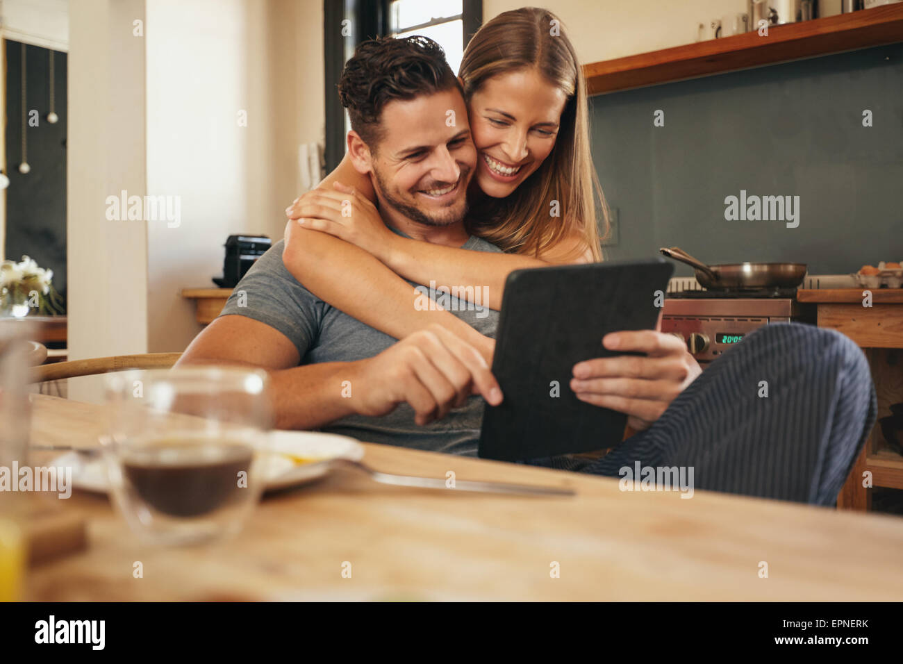 Par sonriendo mientras leen un equipo tablet pc juntos en la mañana en la cocina. Hombre y mujer joven remontando Imagen De Stock
