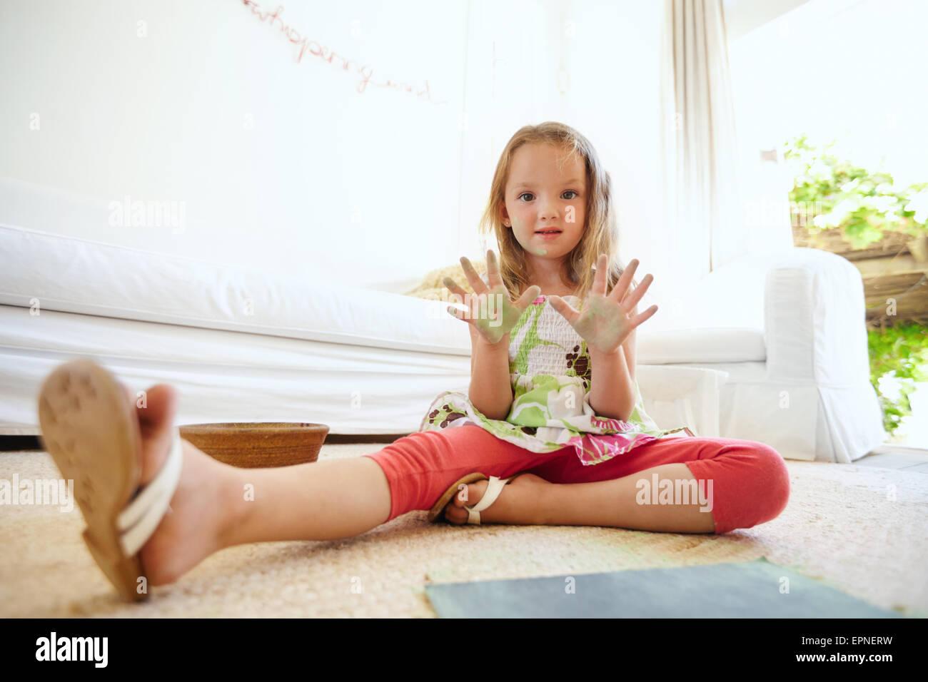 Retrato de hermosa niña divirtiéndose mientras la pintura. Colegiala sentada en el piso en casa mostrando Imagen De Stock