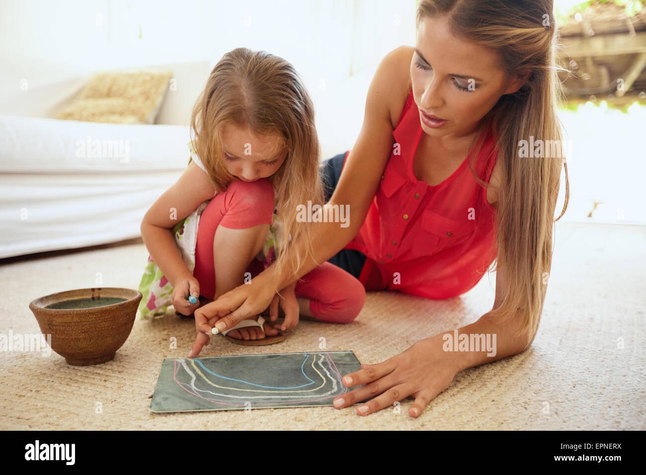 Retrato de madre e hija juntas dibujando con tizas de color, ambos sentados en el piso en la sala a hom Imagen De Stock