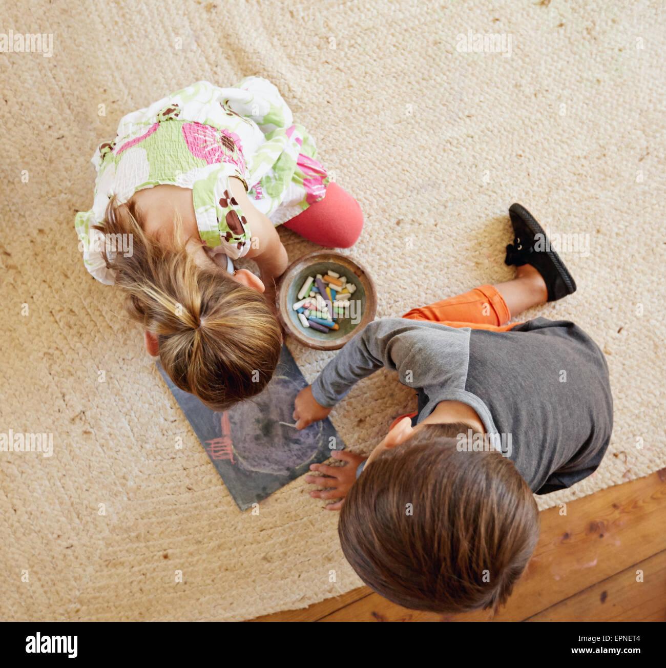 Vista superior de dos niños pequeños sentados en el piso dibujando con tizas de colores. Imagen De Stock