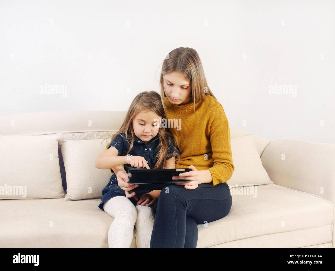 Niña con su madre utilizando dispositivo tableta en el sofá en casa, familia feliz, concepto tecnológico Imagen De Stock