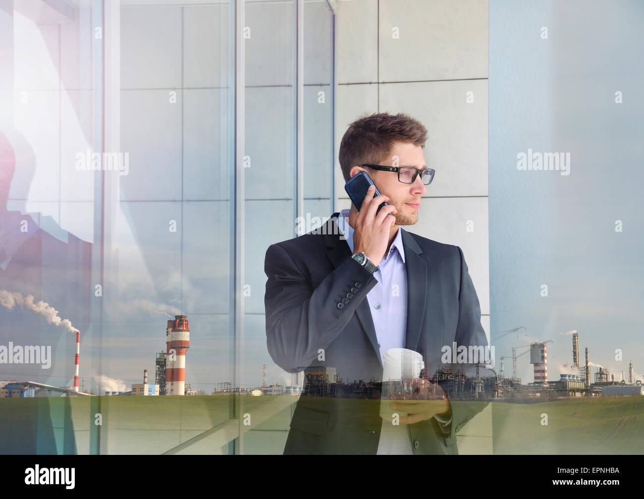 Doble exposición de empresario atractivo urbano e industrial con dispositivo de teléfono de fondo de construcción Imagen De Stock