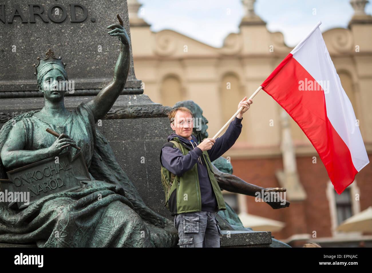 Joven con la bandera polaca cerca de Mickiewicz monumento en la plaza principal de Cracovia, Polonia. Imagen De Stock