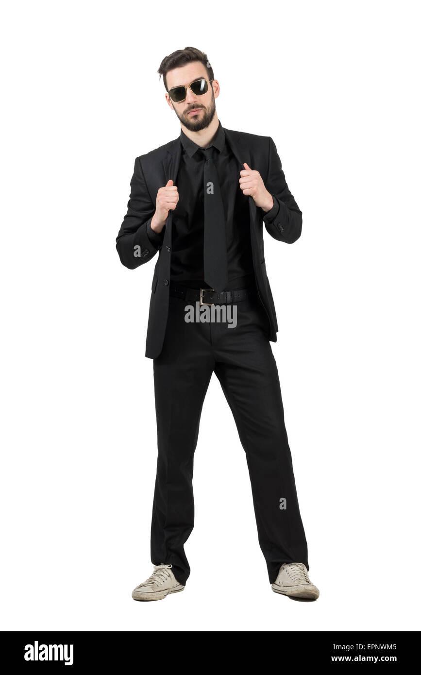 Misterioso hombre barbado en traje negro y zapatillas blancas sosteniendo  el collar. Longitud de cuerpo completo retrato aislado sobre blanco 30d5101c8d5