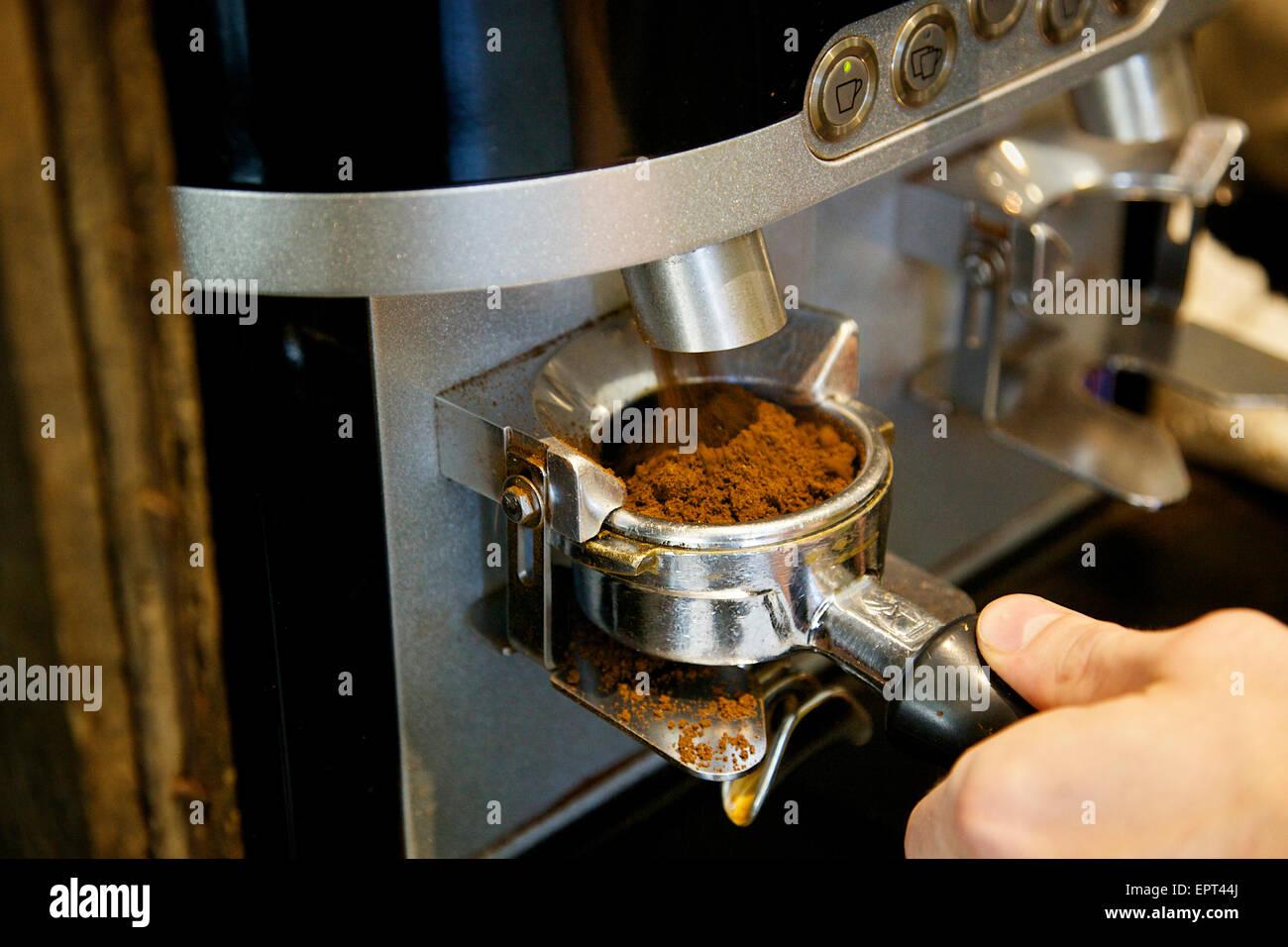 Molinillo de café automática Cesta Portafilter llenado en la cafetería. Foto de stock