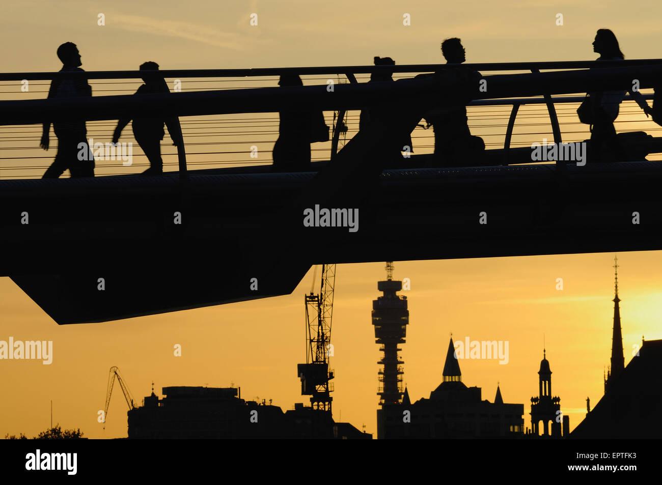 Los peatones en silueta en el Puente del Milenio, Londres, Reino Unido, al atardecer, con edificios en segundo plano. Imagen De Stock