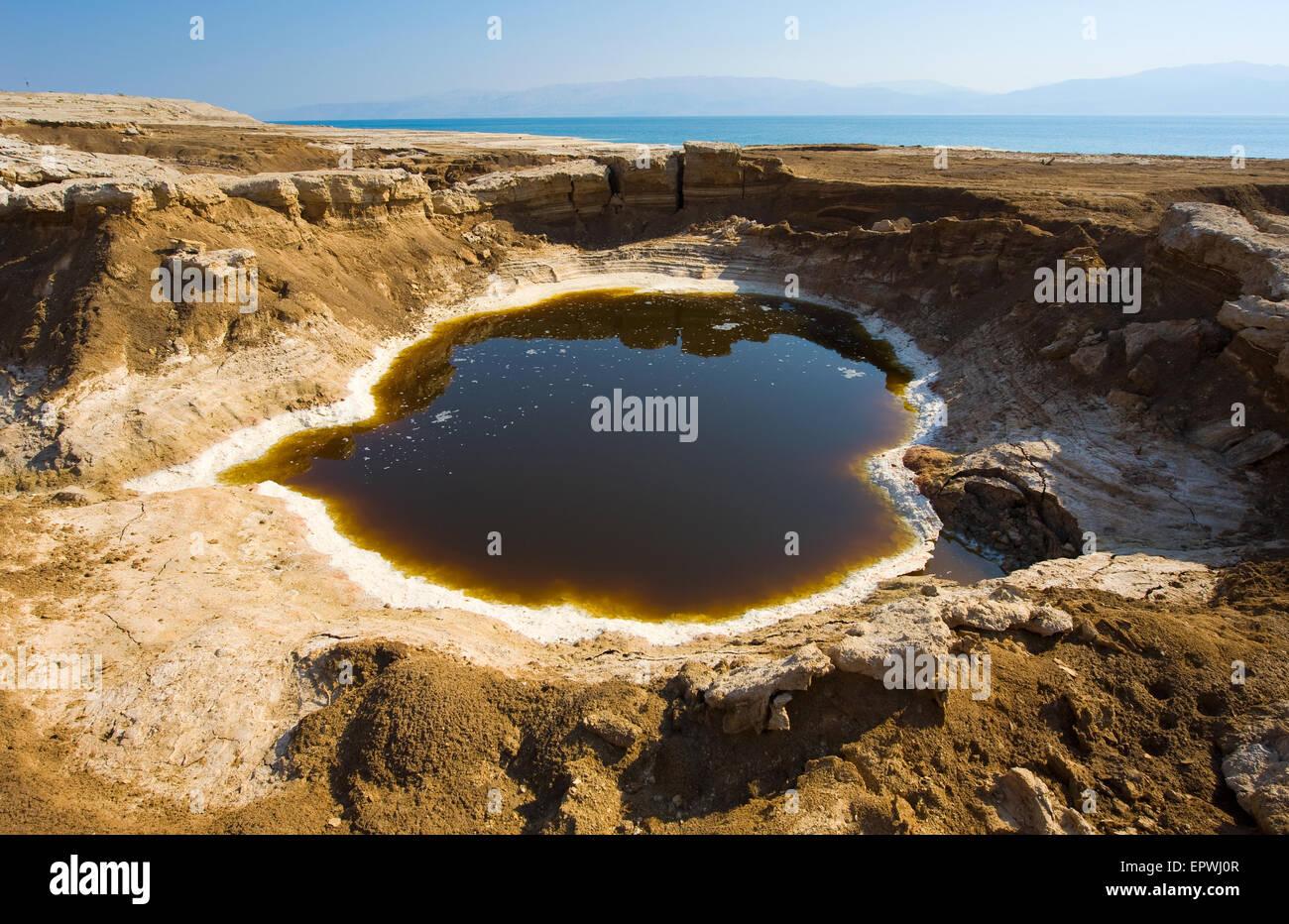 Sumidero o a cielo abierto en la orilla del mar muerto al final del verano, cuando el nivel de agua es por el menor Foto de stock