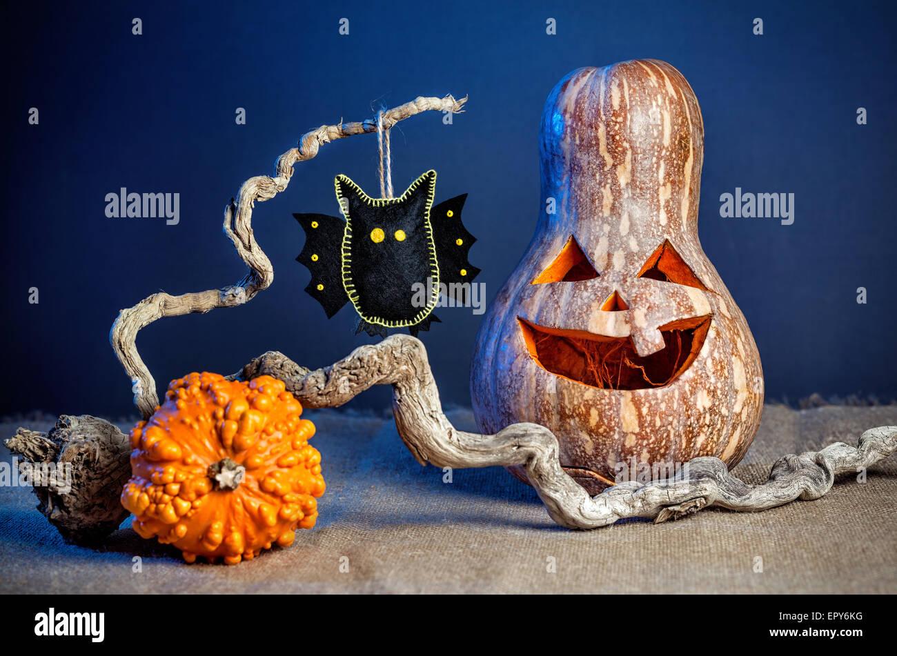 Calabaza tallada y black bat de fieltro en la sucursal en la fiesta de Halloween Imagen De Stock