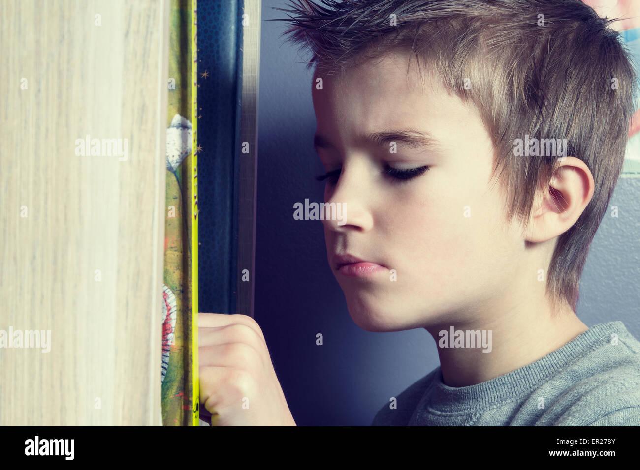 Niño de 8 años eligiendo un libro en su dormitorio Imagen De Stock
