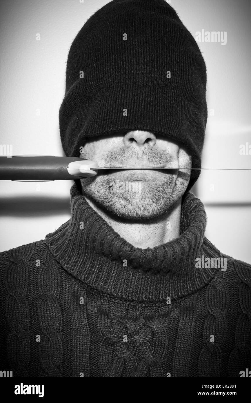 Hombre concepto oculto con un cuchillo en la boca Imagen De Stock