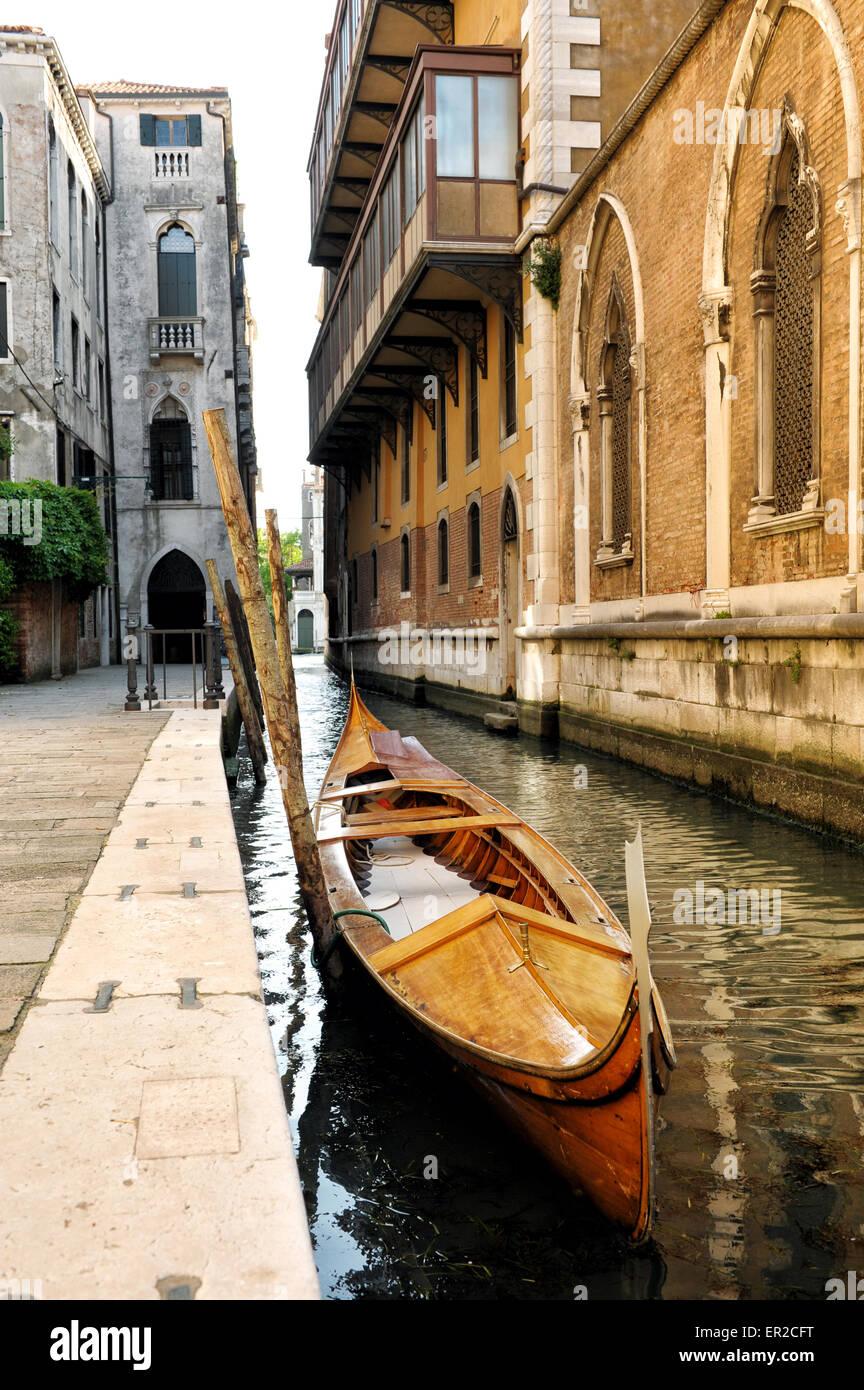 Icónica góndola de madera atados en estrecho Canal bordeado con edificios, Venecia, Italia Imagen De Stock