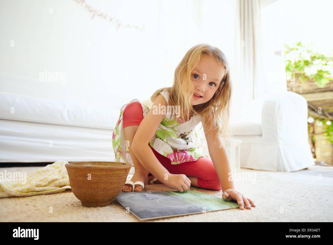 Retrato de niña inocente pintar un cuadro. Colegiala sentada en el suelo colorear sonriendo mirando a la cámara. Imagen De Stock