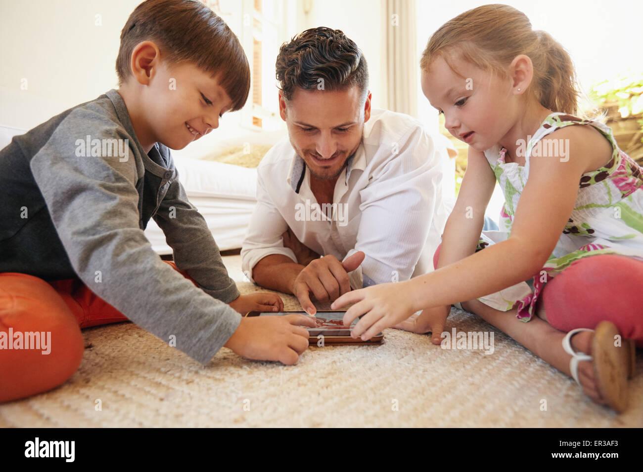 El padre con el hijo e hija sentado en el piso con la tableta digital en el interior. Una joven familia feliz junto Imagen De Stock