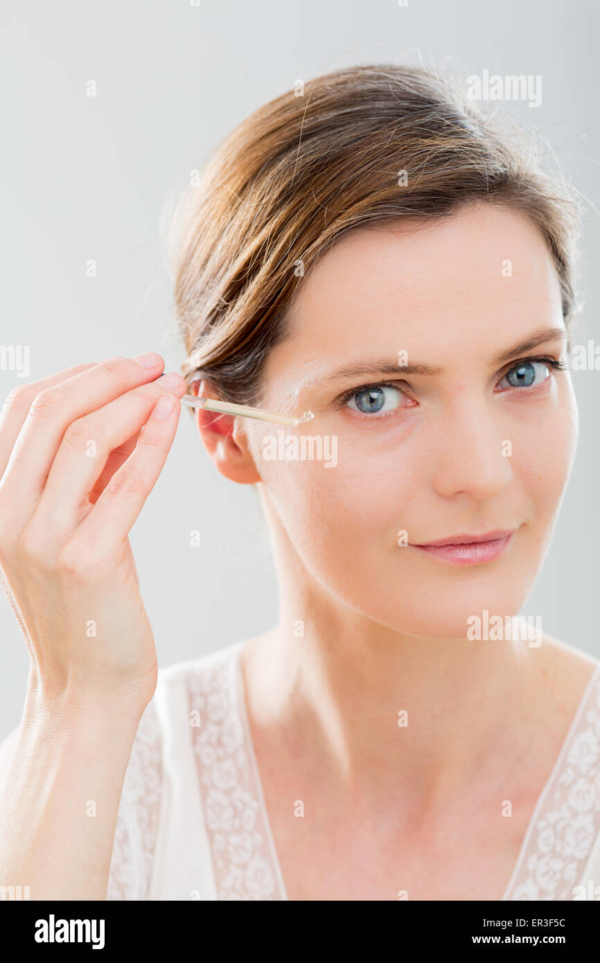 Mujer utilizando suero contorno de ojos. Imagen De Stock