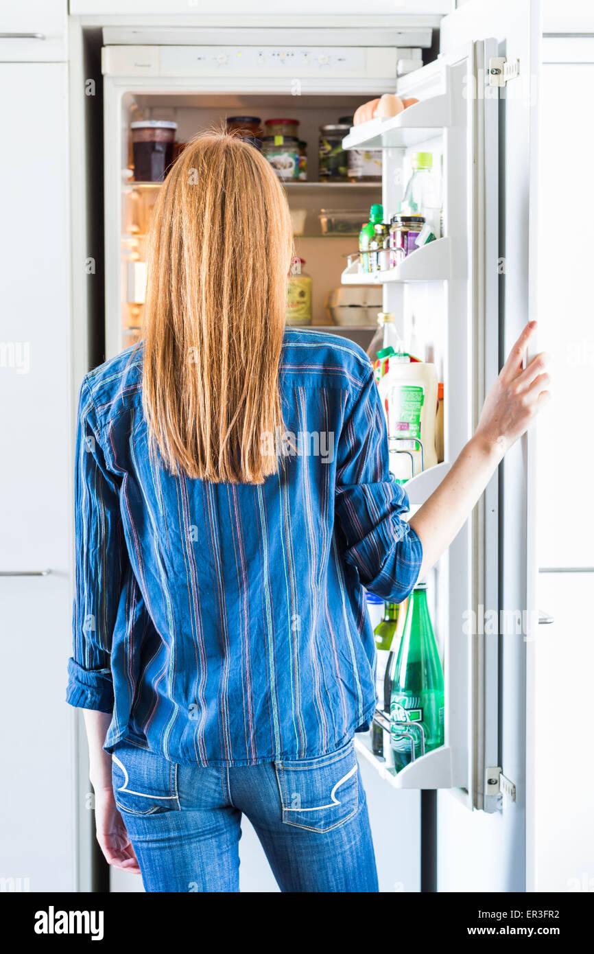 Mujer en frente de un refrigerador. Imagen De Stock