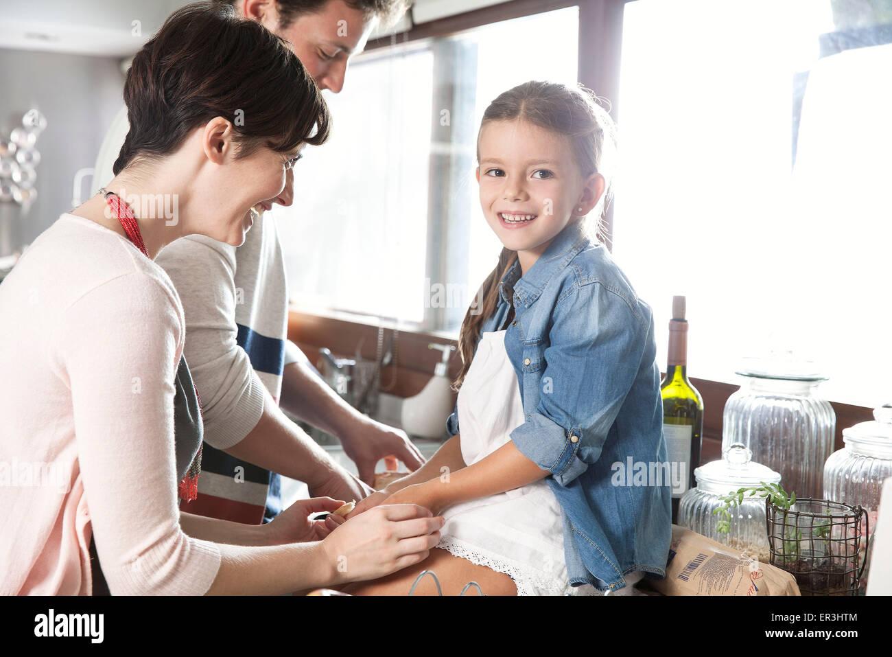 Familia pasar tiempo juntos en la cocina, la muchacha sentada contra la celebración de manos de la madre Imagen De Stock