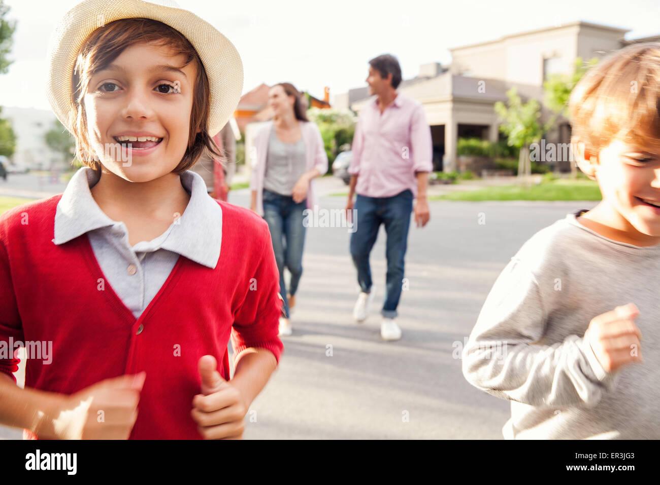 Los niños corriendo por la calle, la familia caminando detrás de ellos Imagen De Stock