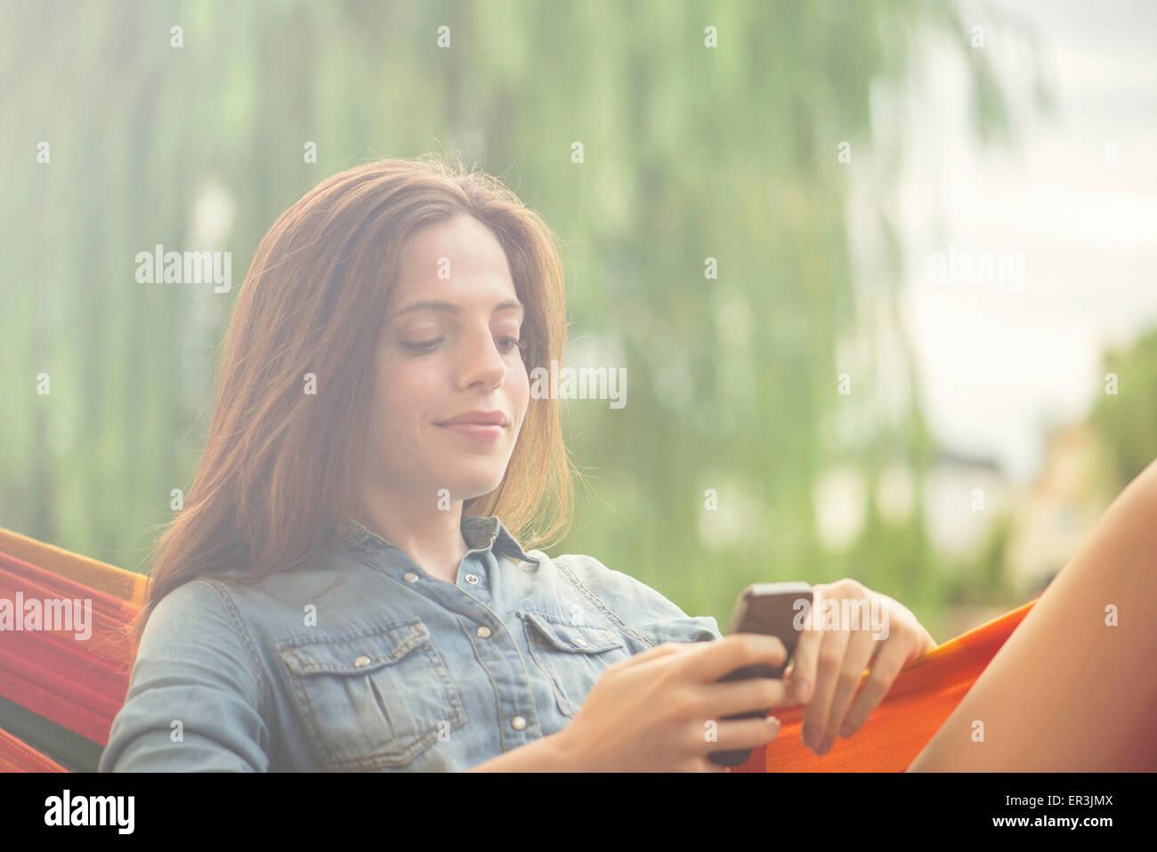 Mujer en Hamaca reclinable con el smartphone Imagen De Stock