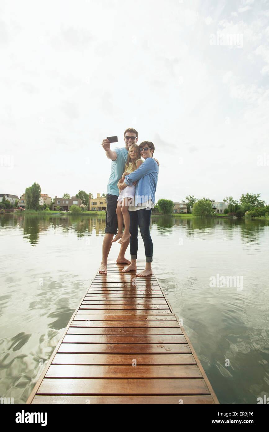 Familia con hija joven de pie junto al final del lago pier teniendo selfie Foto de stock