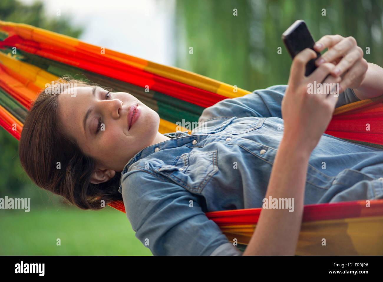 Mujer descansando en una hamaca con el smartphone Imagen De Stock