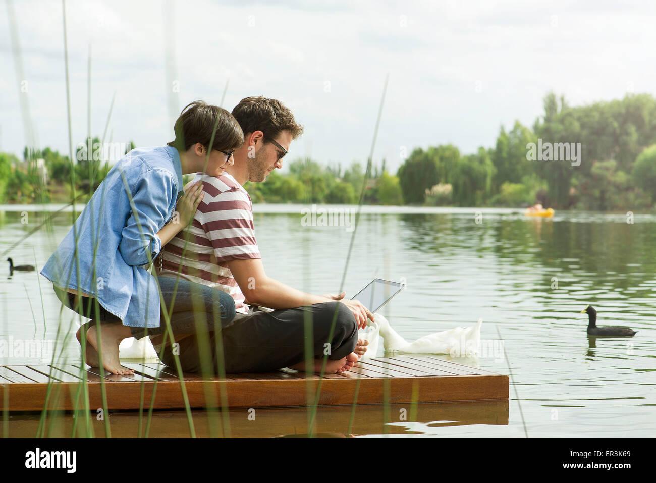 Pareja utilizando equipo portátil en el dock Foto de stock