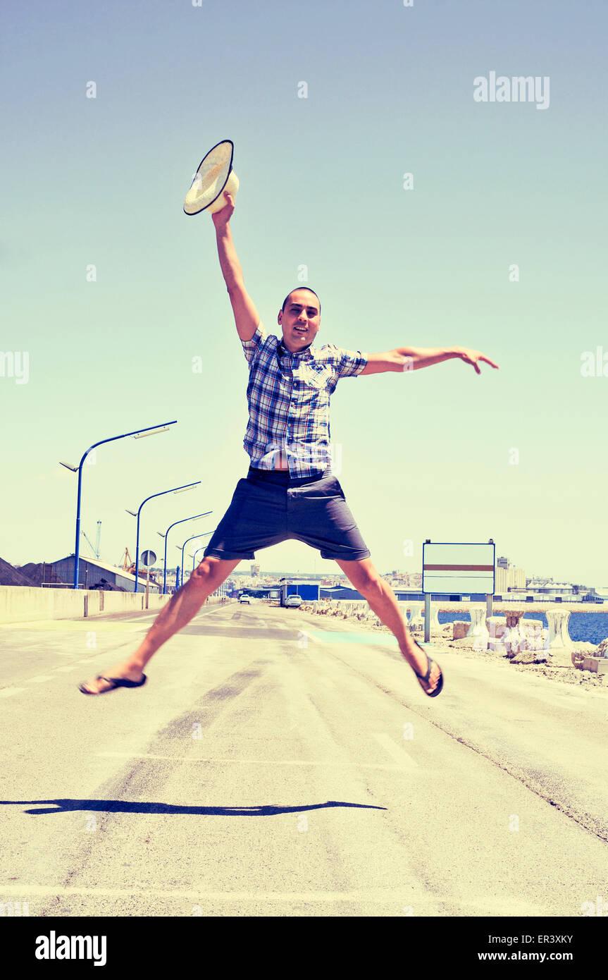 Un joven hombre caucásico con un sombrero de paja en su mano saltando en una carretera sin tráfico cerca Imagen De Stock