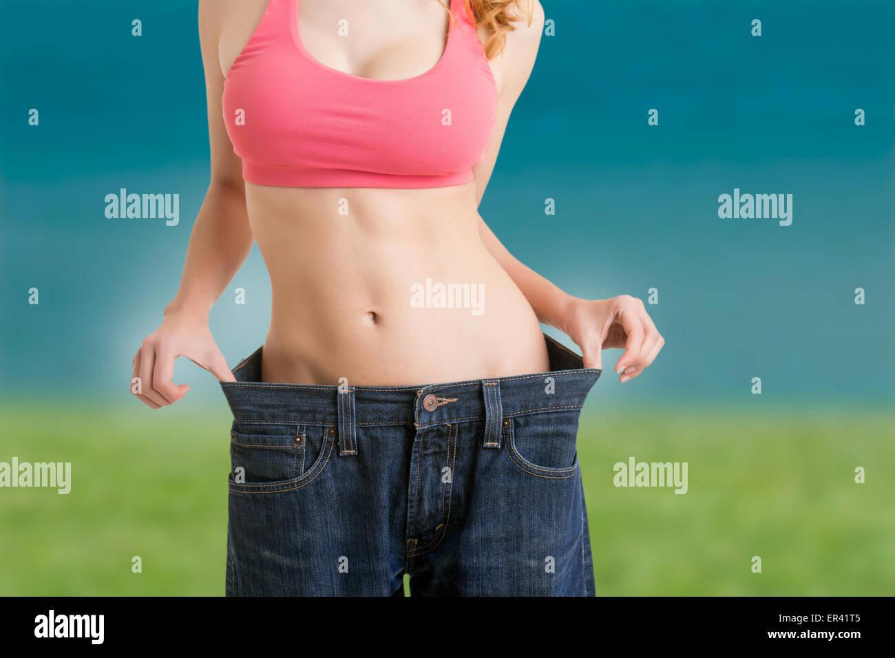 Mujer a ver los resultados de su dieta, en una playa Imagen De Stock