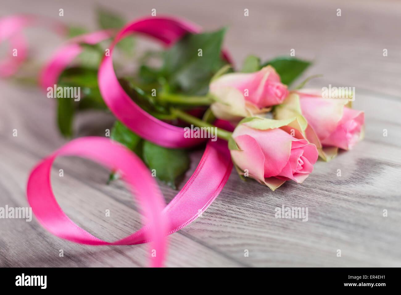 Los tulipanes con un lazo rosado en una mesa de madera Imagen De Stock