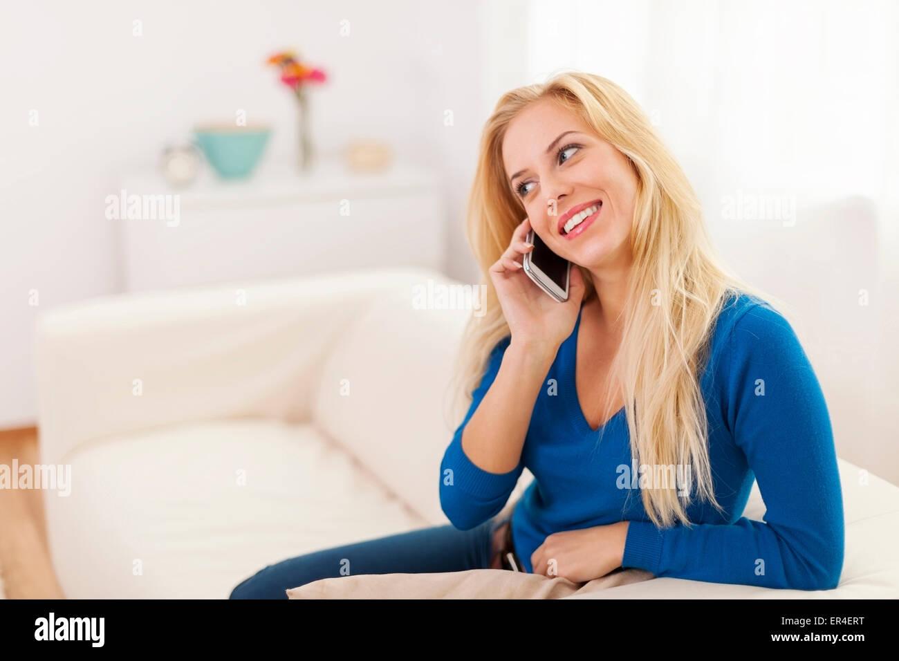 Lindo rubia mujer hablando por teléfono móvil en el hogar Imagen De Stock