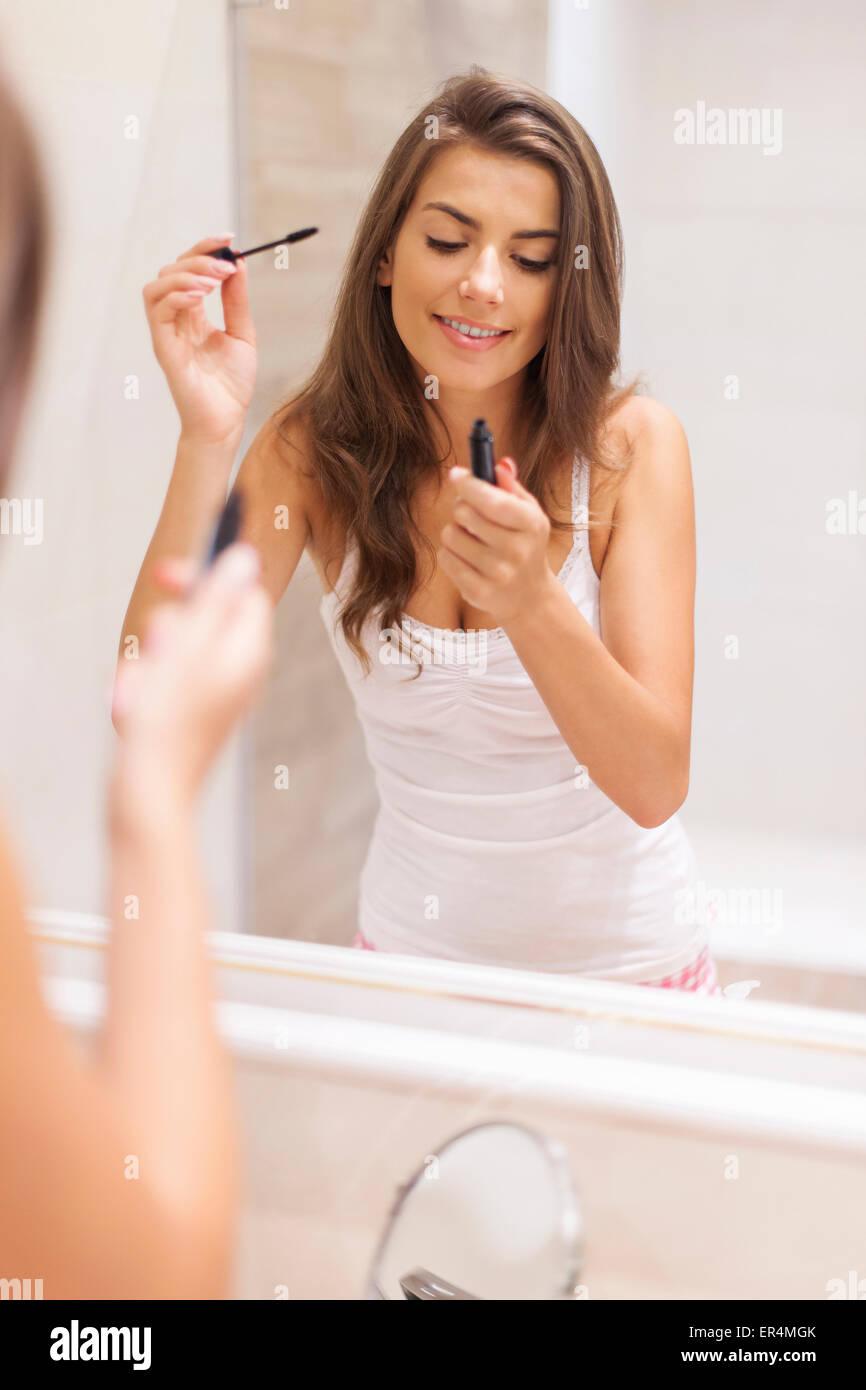 Bella mujer de aplicar el rímel en el baño. Debica, Polonia Imagen De Stock