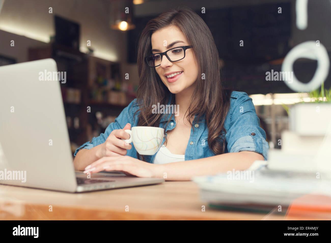 Hermosa mujer hipster con portátil en la cafetería. Cracovia, Polonia Imagen De Stock