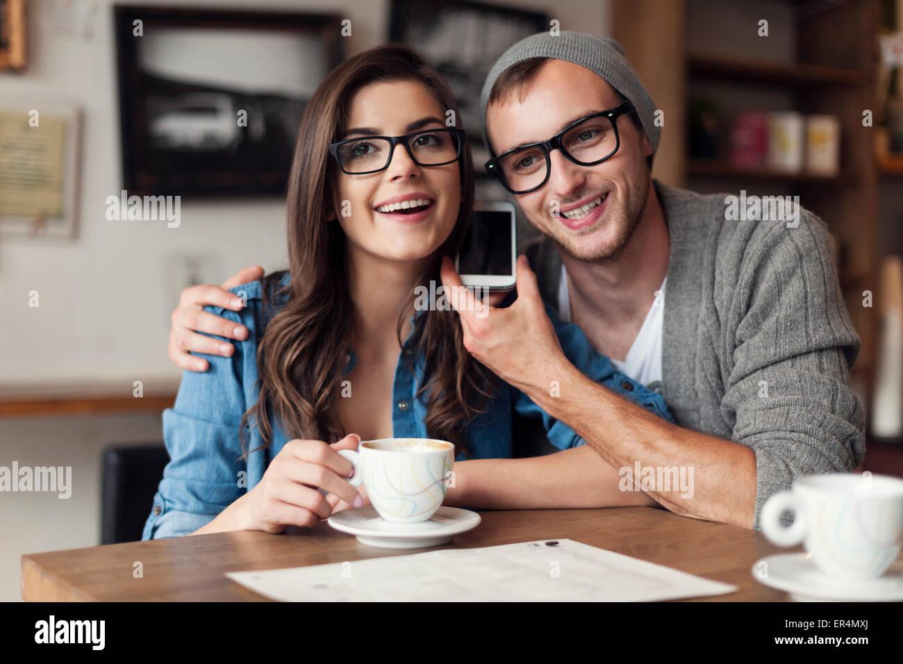 Joven pareja feliz escuchando la voz desde un teléfono móvil. Cracovia, Polonia Imagen De Stock