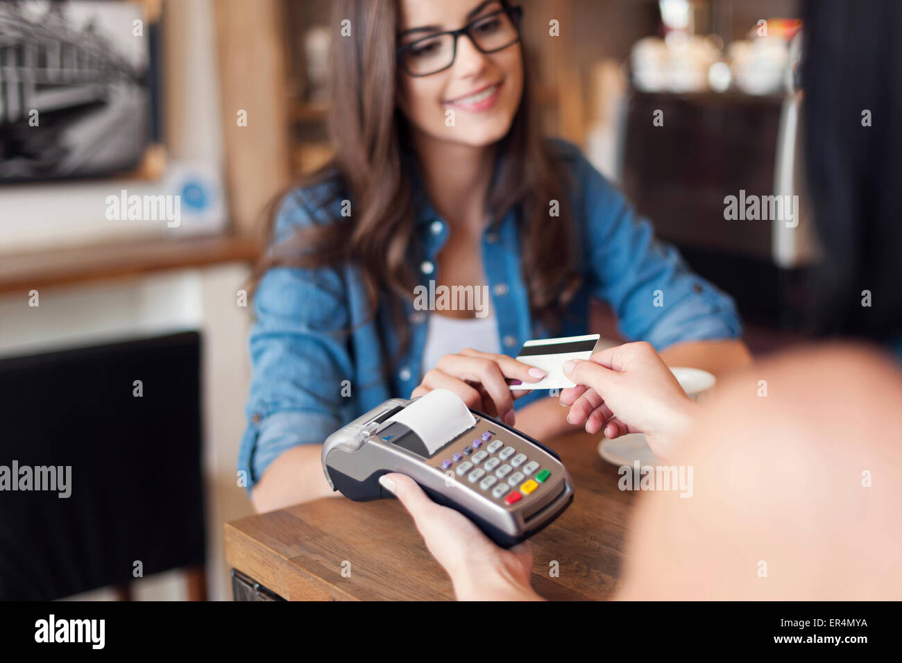 Mujer sonriente café pagando con tarjeta de crédito. Cracovia, Polonia Imagen De Stock