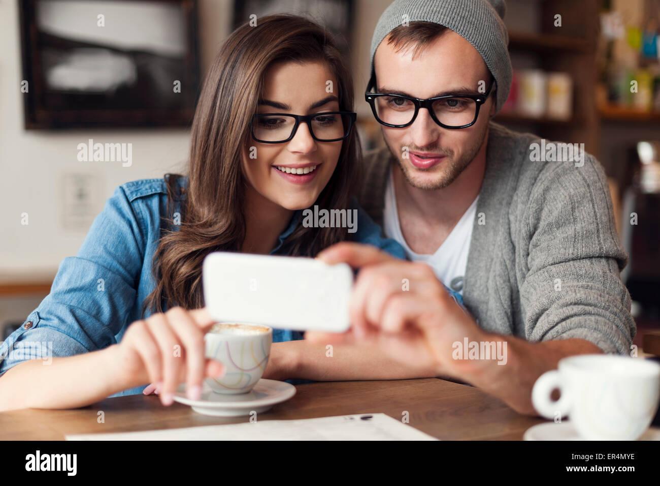Hipster par a través de teléfono móvil en el cafe. Cracovia, Polonia Imagen De Stock