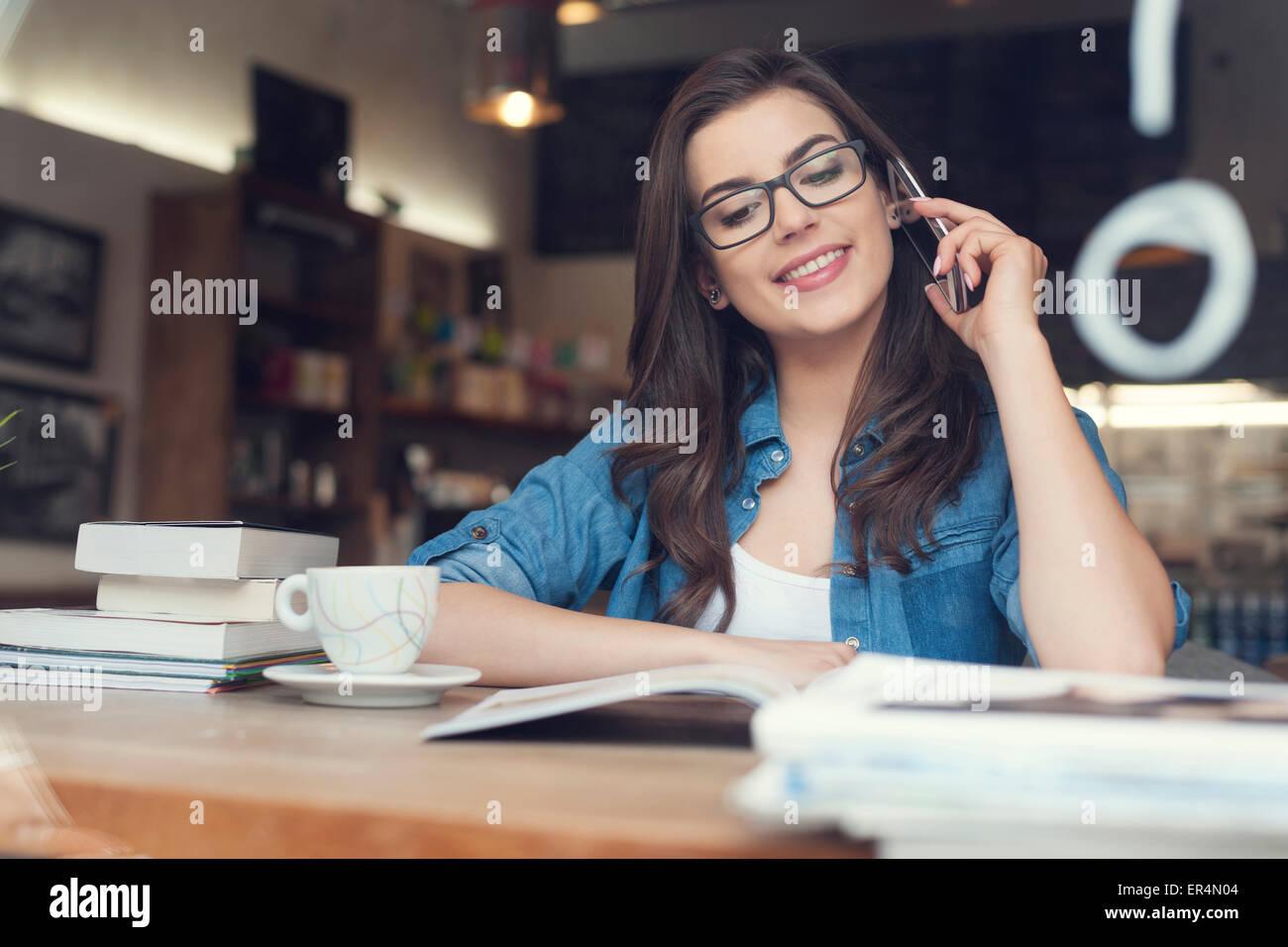 Mujer sonriente hablando por teléfono en el cafe. Cracovia, Polonia Foto de stock