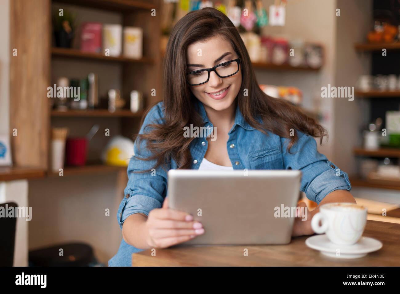 Bella mujer utilizando tablet digital en el cafe. Cracovia, Polonia Imagen De Stock
