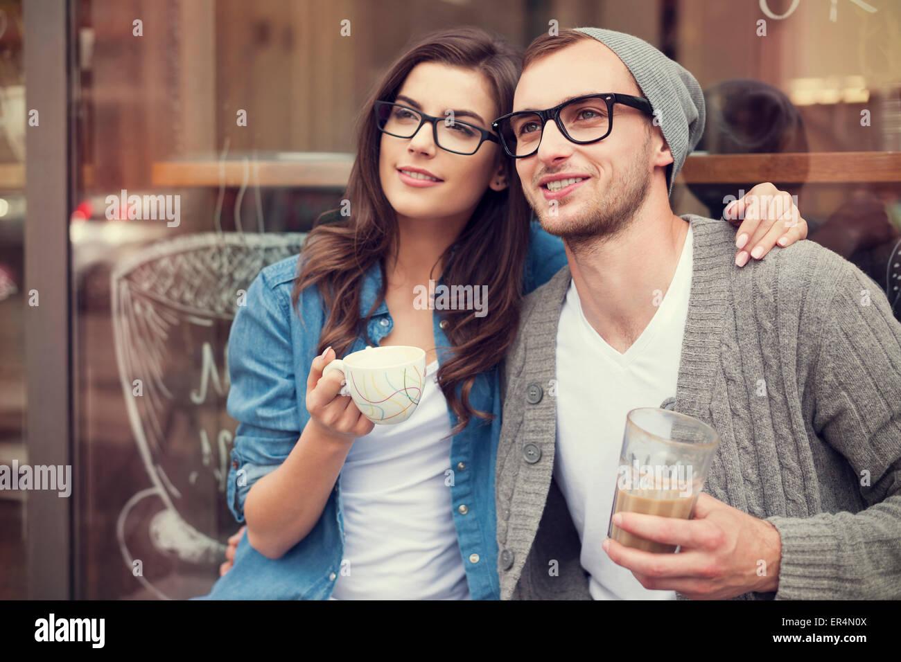 Moda joven pareja beber café fuera de la cafetería. Cracovia, Polonia Imagen De Stock