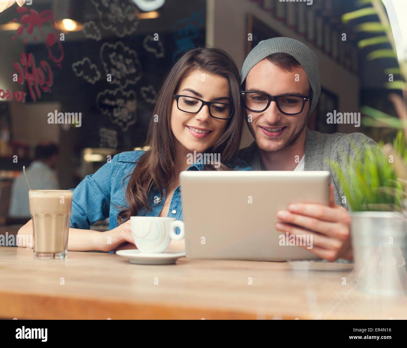 Hipster par disfrutar de conexión inalámbrica a internet en la cafetería. Cracovia, Polonia Imagen De Stock