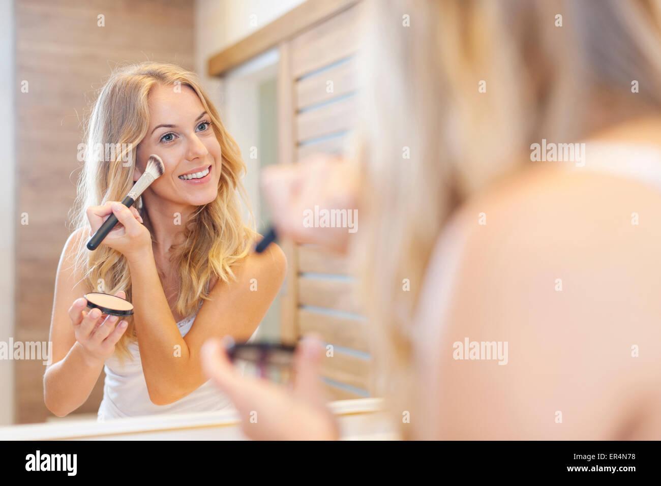 Hermosa mujer rubia haciendo maquillaje delante del espejo. Debica, Polonia Imagen De Stock