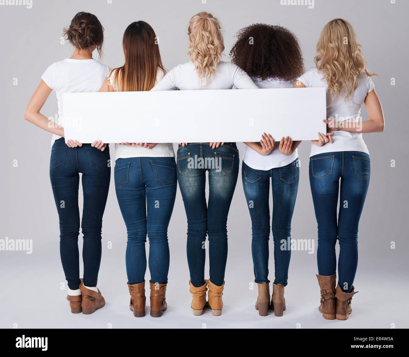 Chicas en jeans sosteniendo pancartas vacías. Debica, Polonia Imagen De Stock