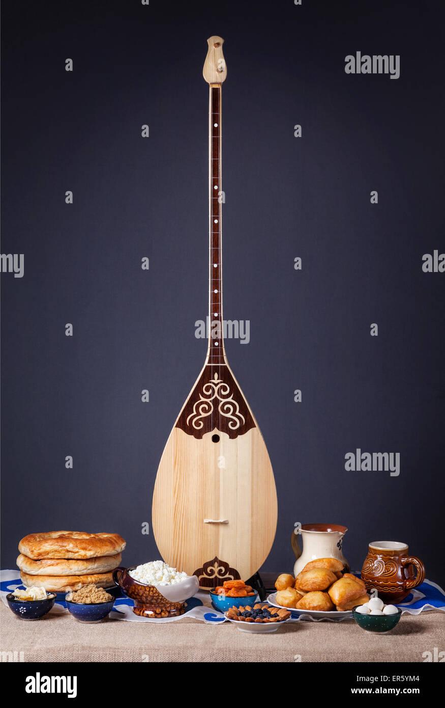 Dombra instrumento kazajo y platos asiáticos en la mesa de fondo gris Imagen De Stock