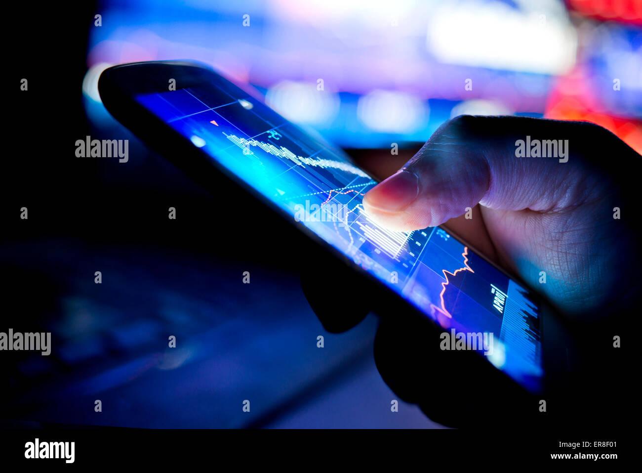 Un hombre de negocios de la ciudad a través de un dispositivo móvil para comprobar las existencias y los Imagen De Stock