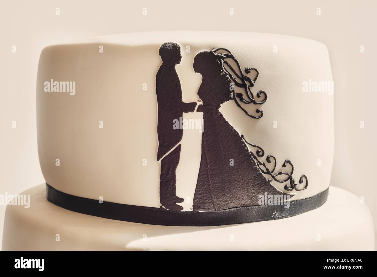 Detalles de un pastel de bodas, azúcar blanco, crema y siluetas negras. Imagen De Stock
