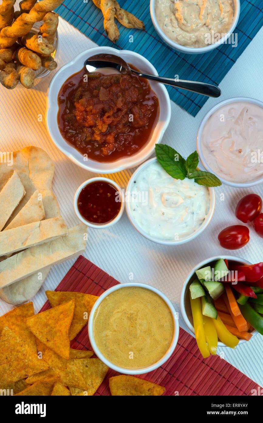 Una selección de salsas con palos de pan partido y otros crudites. Imagen De Stock
