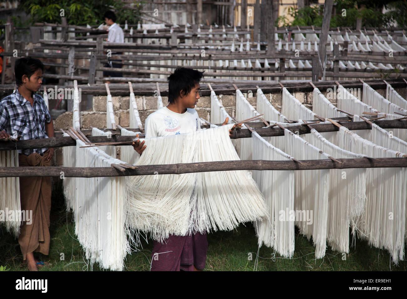 En Hsipaw, Birmania, fideos de arroz recién hecho se colgaban sobre postes para secar al aire libre después Imagen De Stock