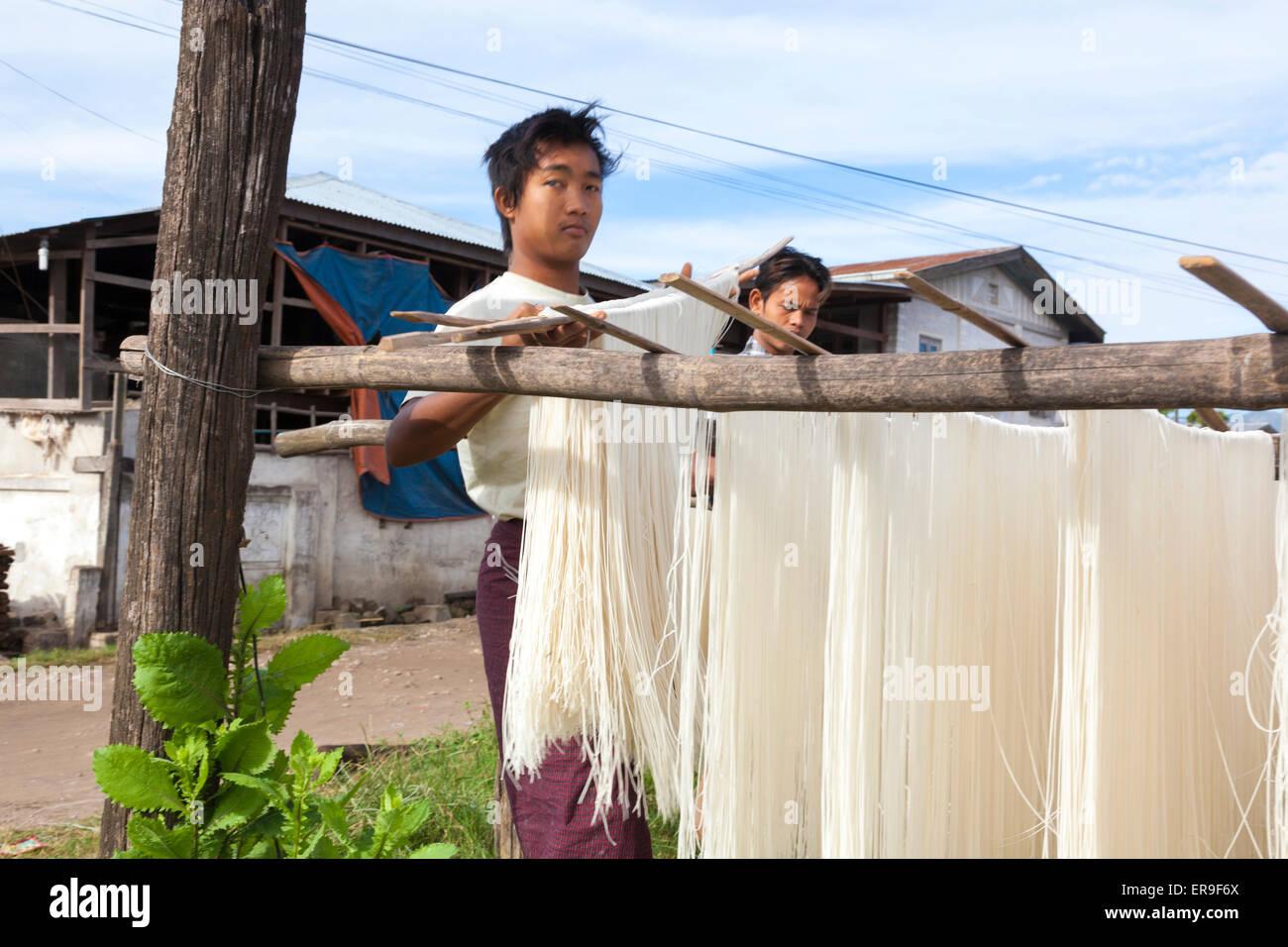 En Hsipaw, Birmania, fideos de arroz hechas frescas se colgaban sobre postes para secar al aire libre después Imagen De Stock